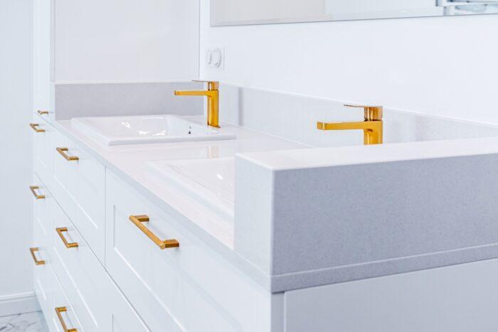 Białe meble łazienkowe i złota armatura.
