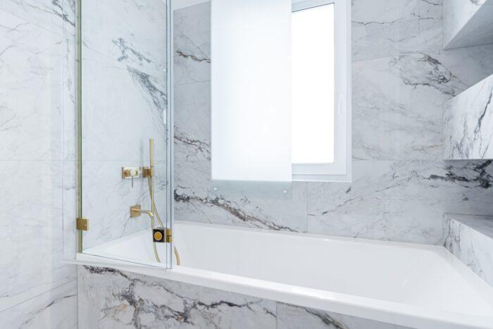 Łazienka z płytkami imitującymi marmur.